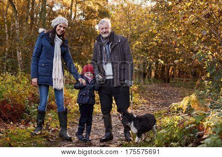 Multi Generation Family Take Dog For Walk In Fall Landscape
