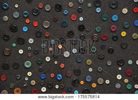 Many various buttons layered on a dark floor