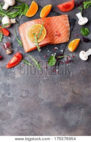 Delicious portion of fresh salmon fillet with aromatic herbs, spices and vegetables - healthy food, diet or cooking concept, flat lay, copy space