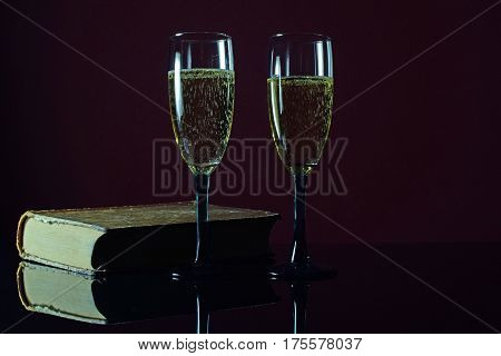 Two glass of champagne and an old book