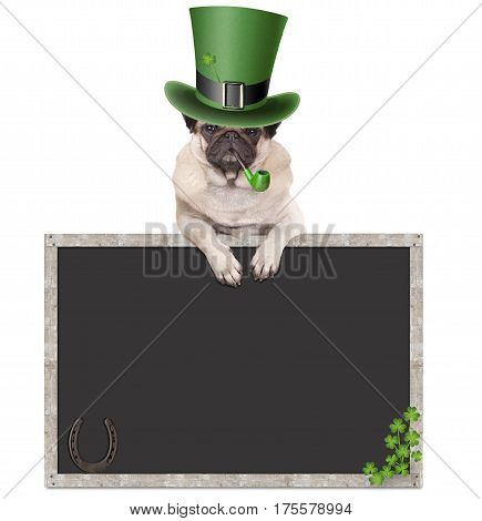lovely cute pug puppy dog with leprechaun hat for st. patrick's day smoking pipe leaning on blank chalkboard sign with horseshoe and shamrock isolated on white background