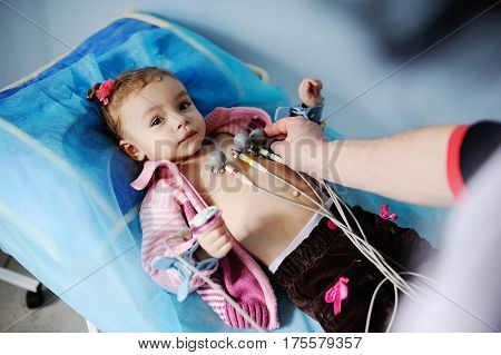 baby girl cute doctor makes an electrocardiogram close up.
