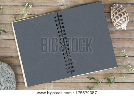 Black paper notebook on rustic wooden background with natural decor. Black notepad with blank page. Rustic artwork mockup. Shabby chic banner template. Vintage flat lay composition on timber texture