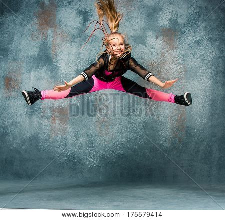 Young girl break dancing in jump on gray wall stidio background.