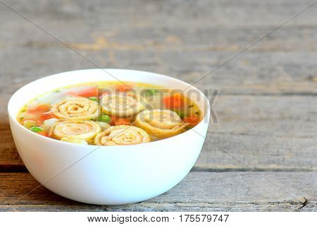 Easy vegetable soup with omelette in a plate isolated on vintage wooden background. Soup with omelette, carrot, peas, leek, cauliflower and potatoes. Closeup