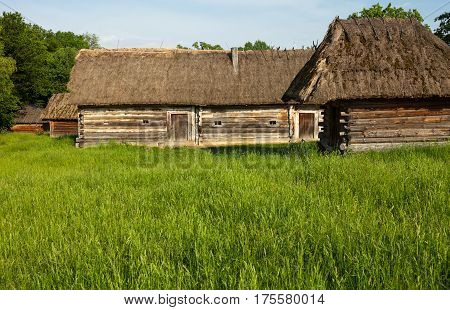Old wooden sheds with moss-grown straw-thatched roofs from the Museum of Folk Architecture and Life of Ukraine in Pyrohiv near Kyiv.