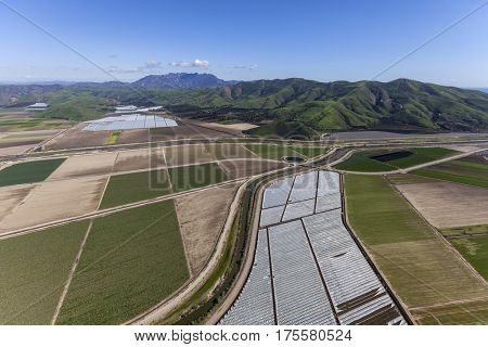 Aerial view of agricultural land and Santa Monica Mountains peaks in Ventura County, California.