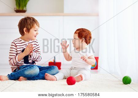 Cheerful Senior Kid Playing With His Junior Toddler Brother At Home