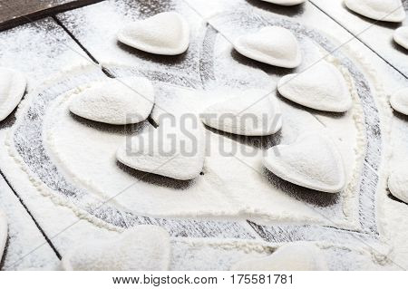 Raw dough in the shape of a heart (pierogi ravioli dumplings) strewing flour laid out on a dark wooden background.