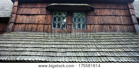 Ancient wooden church (XIX century) from the Western Ukraine in the open-air Museum of Folk Architecture near Kyiv. Windows. Close-up.