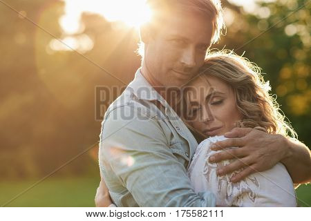 Affectionate young couple smiling and hugging while enjoying a romantic moment together on sunny summer afternoon in a park