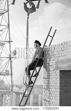 Vintage construction. Vertical monochrome shot of a muscular shirtless vintage handy man sitting relaxing on a ladder at construction site looking away rearview building industry business confident