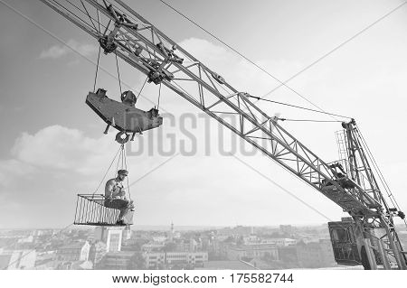 Extreme lunch. Black and white shot of an old fashioned shirtless relaxed construction worker having lunch sitting on a crossbar hanging from the crane high above the city.