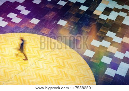 Blurred Abstract Background. Alone silhouette of man walking in a public building hall top view. Motion blur technique of low speed shot. Blur silhouettes of people's. Low speed shutter shot.