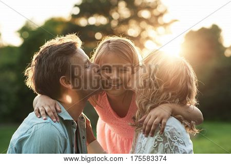 Portrait of a mother and father kissing their smiling little girl on the cheeks while enjoying a sunny summer afternoon together in a park