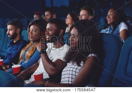 Side view of pretty african curly-haired girl and group of people spending free time in cinema together. Friends watching movie in modern cinema hall and sitting in comfortable seats.