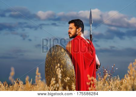 Spartan soldier. Rear view shot of a handsome young male warrior in battle dress standing alone in the field with a spear and a shield under blue summer skies looking toward copy space. Victorious protection concept.