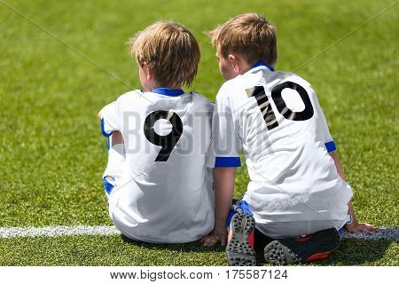 Young Soccer Football Players. Little Boys Sitting on Soccer Pitch. Youth Football Players in White Soccer Jersey