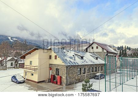 Guest house pension from Romania Busteni Mountain range with pine forest and fog winter time with snow