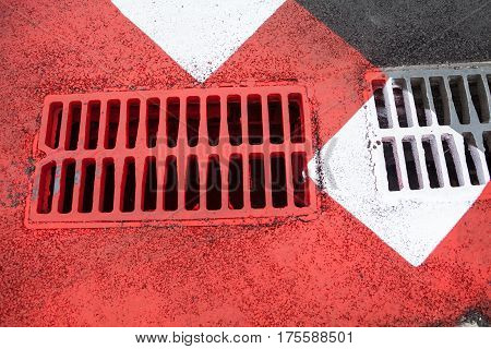 Drain grates on the road with red and white road marking.