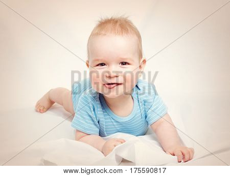 Eight month old baby lying in the bed on white sheet. Cute boy showing tongue