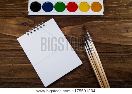 Art palette with brushes and paints on a wooden background