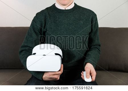Man on sofa holding VR box and remote control. Male person in casual clothes with virtual reality headset at home sits on sofa