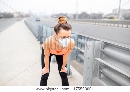Young sports woman in protective mask resting on the road in the city. Exercising in the city with smog
