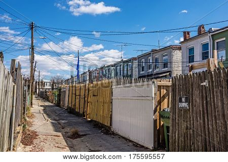 A narrow old road between rows of homes in the historic Northern Baltimore neighborhood of Hampden.