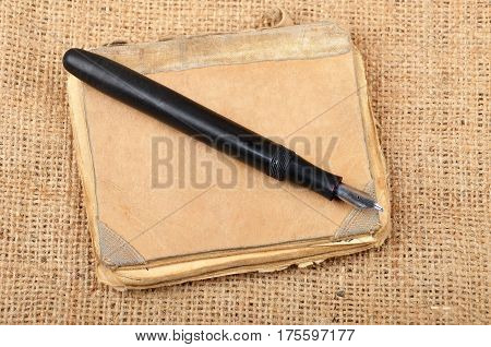 Vintage notepad and ink pen on burlap background