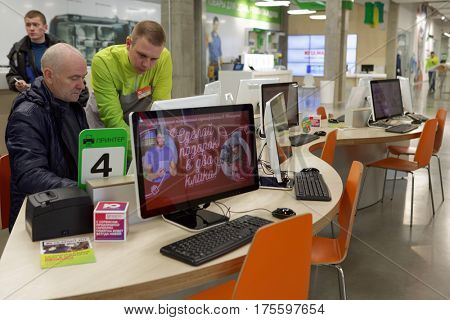 ST. PETERSBURG, RUSSIA - OCTOBER 27, 2016: Manager of Ulmart company helps client to compose his order at the service desk. Ulmart is one of the largest Internet retailers in Russia