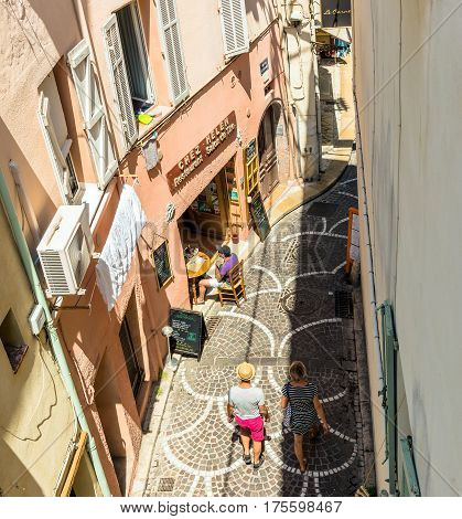 Antibes, France - June 27, 2016: day view of old town street with tourists in Antibes France.