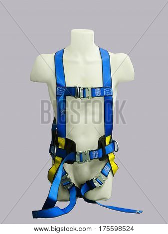 Mannequin in safety harness equipment over gray background