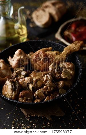 closeup of a frying pan with mushrooms and some pieces of grilled chicken and grilled rabbit, typically eaten in Spain, on a rustic wooden table, with a cruet of olive oil in the background