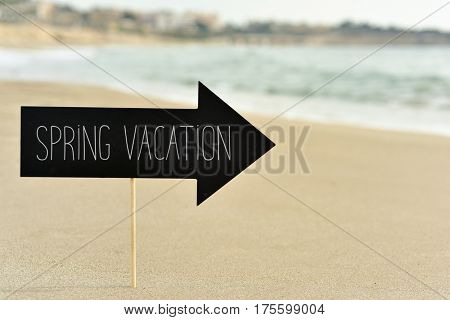 closeup of a black signboard in the shape of an arrow sign with the text spring vacation written in it on the sand of a lonely beach