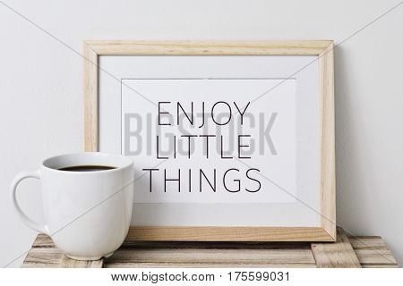 a wooden-framed picture with the text enjoy little things written in it and a cup of coffee, on a rustic wooden surface