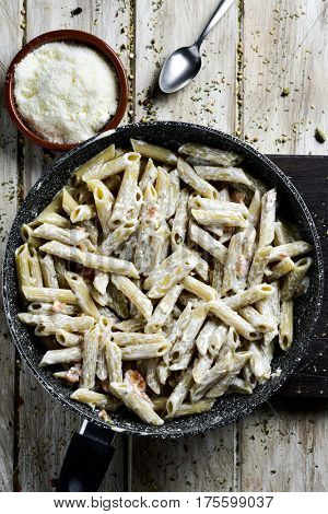 high-angle shot of a frying pan with penne with salmon, cream and cheese, and an earthenware bowl with grated Parmigiano cheese on a rustic wooden table
