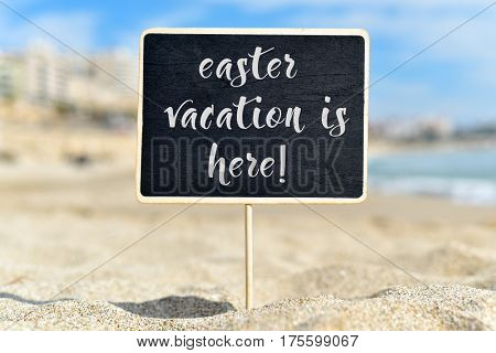closeup of a black signboard with the text easter vacation is here written in it, on the sand of a beach