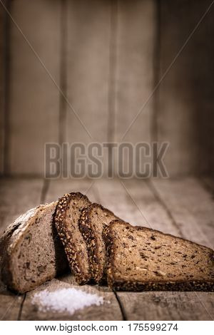 traditional german dark bread sliced on a rustic wooden background