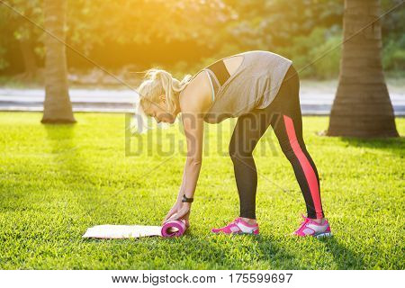 Young Fitness Girl With Ponytail Rolling Pink Mat