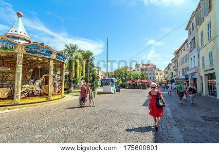 Antibes, France - June 27, 2016: day view of Place des Martyrs de la Resistance with tourists and carousel in Antibes, France.