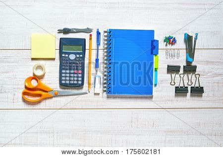 View of a wooden table with a notebook, pen, pencil, rubber, scissors, sellotape, calipers, stapler, clips, pins and a calculator in a nice order