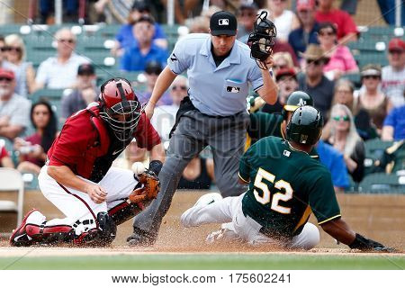 SCOTTSDALE, AZ-MAR 6: Arizona Diamondbacks Miguel Montero misses the tag on Oakland Athletics outfielder Yoenis Cespedes at Salt River Fields at Talking Stick on March 6, 2014 in Scottsdale, Arizona.