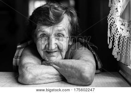 Granny is sitting near the window in the kitchen. Black and white portrait.