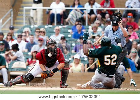 SCOTTSDALE, AZ-MAR 6: Arizona Diamondbacks Miguel Montero misses the tag on Oakland Athletics Yoenis Cespedes (52) at Salt River Fields at Talking Stick on March 6, 2014 in Scottsdale, Arizona.