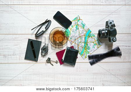 View of a wooden table with a map, watch, passport, notebook, smartphone, keys, old camera, film, pen, wallet, sunglasses and a cup of coffee on it