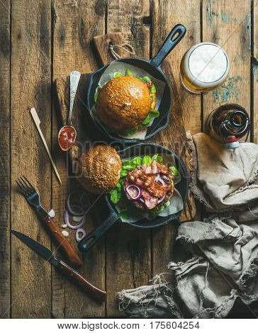 Homemade beef burgers with crispy bacon and fresh vegetables in small cast iron pans and glass of wheat beer on rustic board over old wooden background, top view, vertical composition