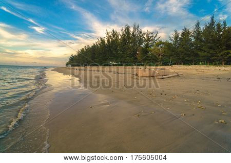 Tropical beach landscape during sunset with beautiful scenic view on sea and coastline with trees and sunset sky in Labuan island, Malaysia.