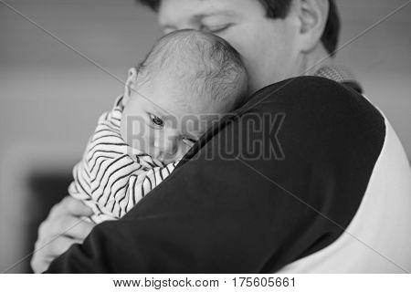 Happy proud young father having fun with newborn baby daughter, family portrait togehter. Dad with baby girl, love. New born child looking on dad. Bonding, family, new life. In black white