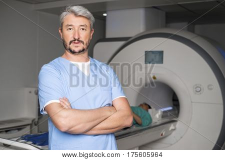 Doctor Standing Arms Crossed With Patient On CT Scan Machine